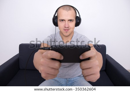 young handsome man on couch playing games or watching movie on mobile phone - stock photo