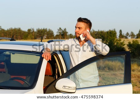 Young handsome man opened the door of his car. Man speaks by phone. Always connected.