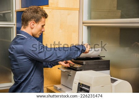 Young Handsome Man Operating High-Tech Photocopier Machine at the Office. - stock photo