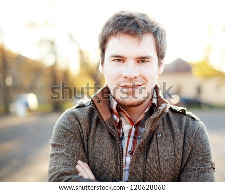 Young handsome man outdoors in fall clothing with autumn natural surroundings