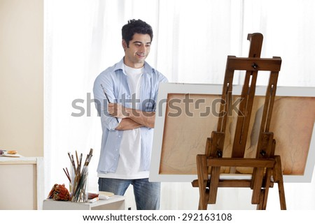 Young handsome man painting at an easel - stock photo