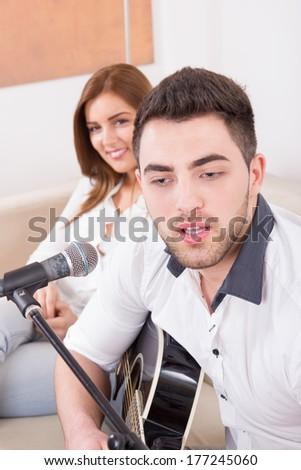 young handsome man playing guitar to girl