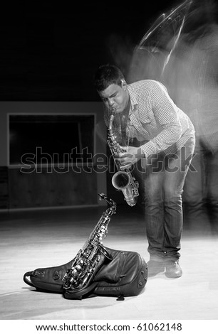 Young handsome man playing music on saxophone. black background - stock photo