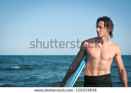 Young handsome man portrait at the sea with surfboard.