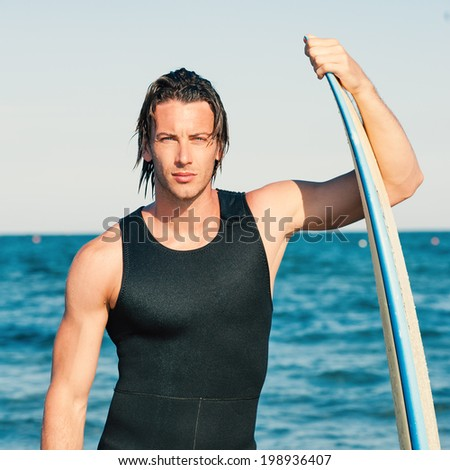 Young handsome man portrait at the sea with surfboard. Filtered image.