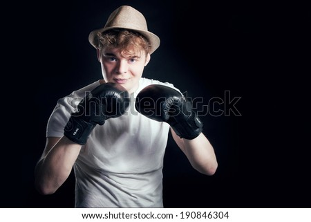 Young handsome man posing in boxer gloves and hat on black background.