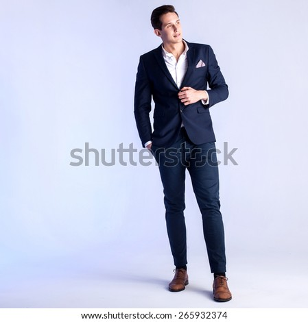 Young handsome man posing in studio wearing fashionable suit. - stock photo
