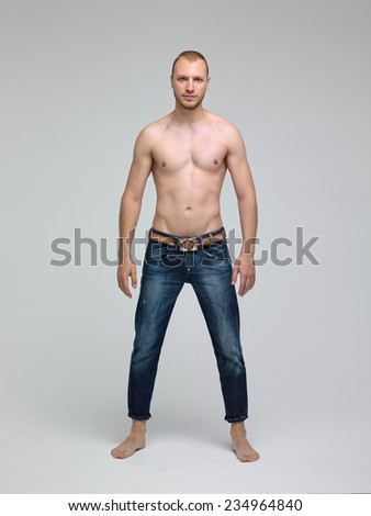 Young handsome man posing in the studio in jeans and with a naked torso - stock photo