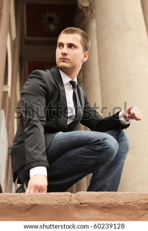young handsome man posing near old theater - stock photo