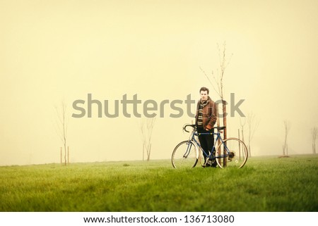 Young handsome man posing on the green meadow with vintage bike - stock photo