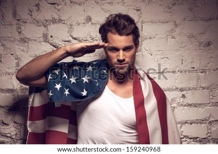 Young handsome man posing with American flag. Saluting like soldier - stock photo