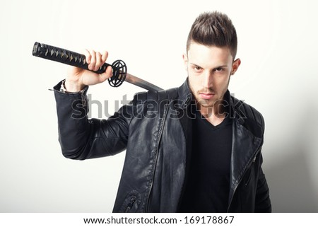 Young handsome man posing with samurai sword. Fashion photo
