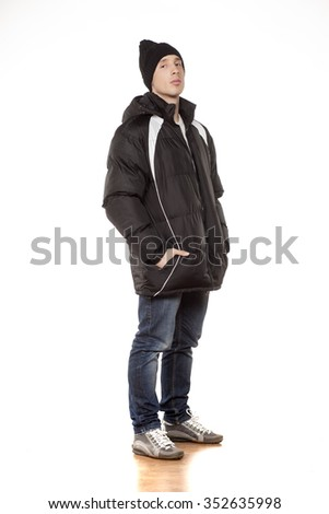 young handsome man posing with winter jacket and woollen cap - stock photo