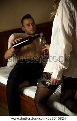 Young handsome man pouring the wine to his sexy girlfriend - stock photo