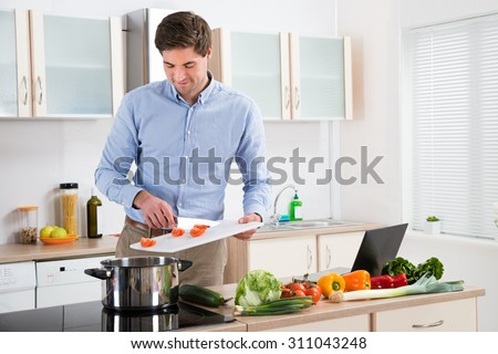 Young Handsome Man Preparing Food In Kitchen At Home - stock photo