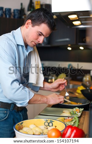 Young handsome man preparing lunch in kitchen  - stock photo