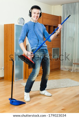 Young handsome man pretending to play guitar with broom while cleaning - stock photo
