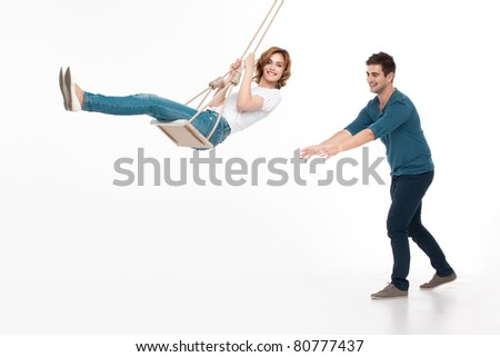 young handsome man pushing his girlfriend on a swing