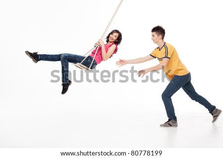 young handsome man pushing his girlfriend on a swing - stock photo
