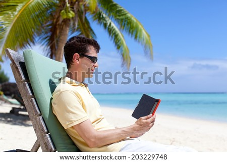 young handsome man reading electronic reader at the beach - stock photo
