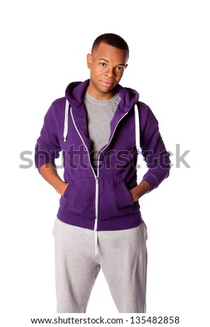 Young handsome man ready for sports wearing purple hooded sweatshirt and gray training pants, isolated. - stock photo