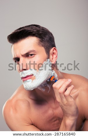 Young handsome man shaving with foam and razor over gray background