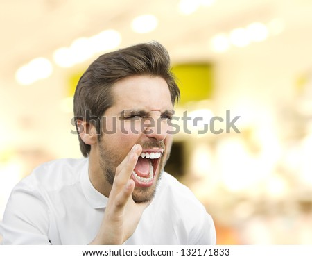 young handsome man shouting in a market