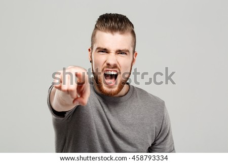 Young handsome man shouting over grey background. Copy space.