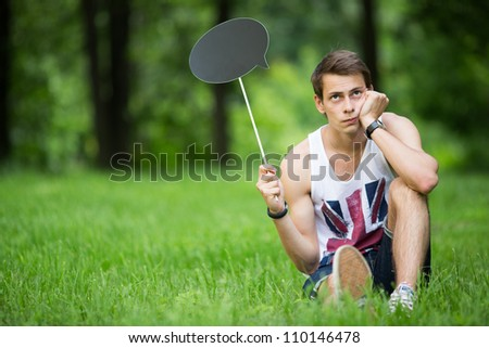 Young handsome man sits on the grass with plate