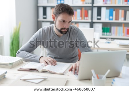 Young handsome man sitting at office desk, studying a book and connecting to internet using a laptop
