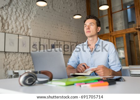 young handsome man sitting at table in co-working office, working at laptop, work place, thinking, writing diary book