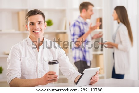 Young handsome man sitting at the table and using digital tablet at office. - stock photo