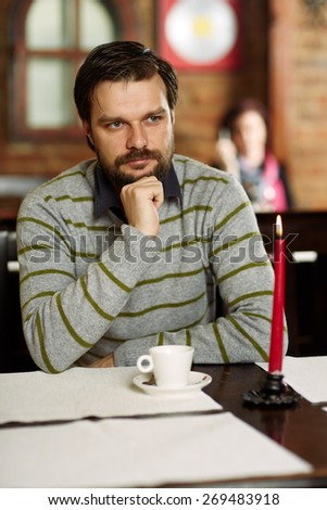 Young handsome man sitting in a restaurant and drinking coffee - stock photo