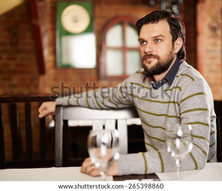 Young handsome man sitting in a restaurant and looking away - stock photo
