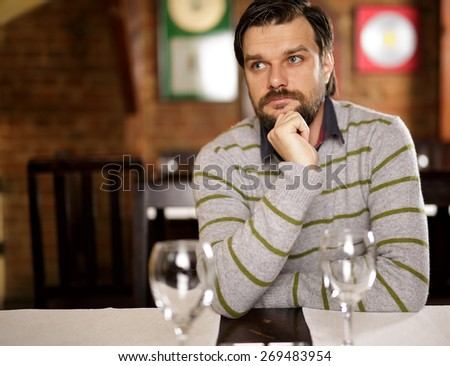 Young handsome man sitting in a restaurant and looking away