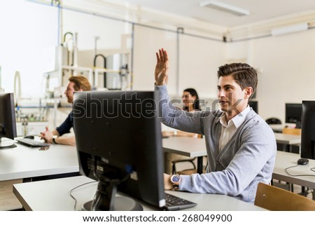 Young handsome man sitting in front of a pc raising hand - stock photo