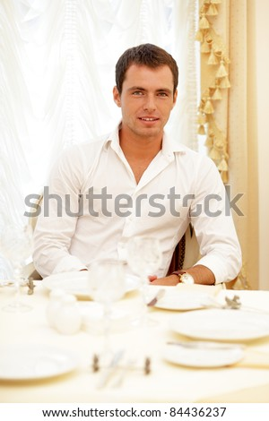 Young handsome man sitting in the restaurant - stock photo