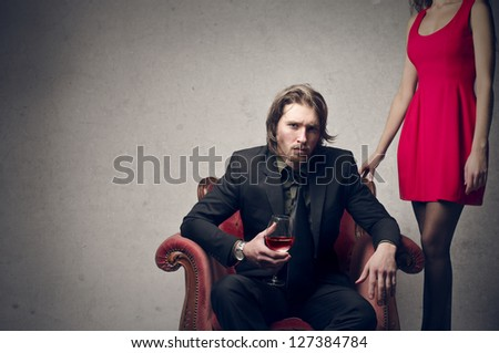 young handsome man sitting on the chair with a glass of red wine and beautiful woman behind - stock photo