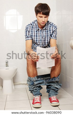 Young handsome man sitting on toilet and reading magazine. - stock photo