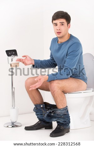 Young handsome man sitting on toilet. guy without toilet paper upset and made helpless gesture - stock photo
