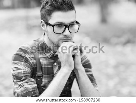 young, handsome man sitting pensively, dressed in the style of hipster - stock photo