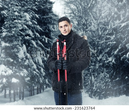 Young handsome man skier wearing black fur hood winter jacket Alaska and pants holding sticks in snowy forest - stock photo