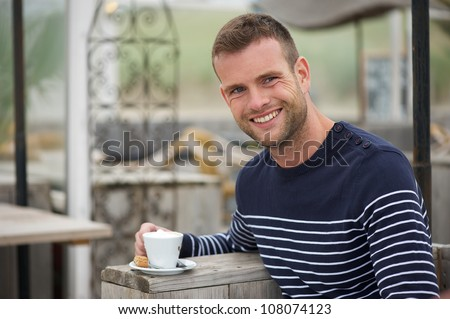 Young handsome man smiling and drinking coffee at a seaside restaurant. He is happy and looking at camera