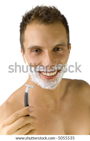 Young, handsome man smiling and looking at camera. Holding safety razor. White background, front view