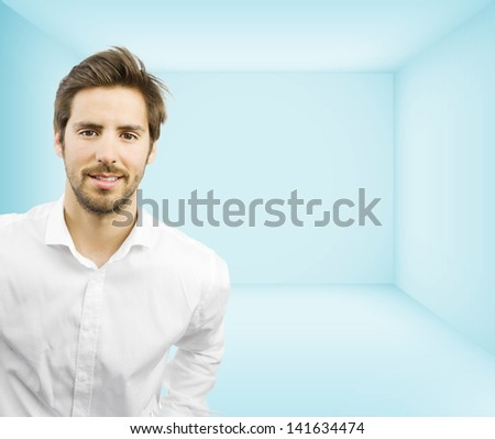 young handsome man smiling in an empty room to your object - stock photo