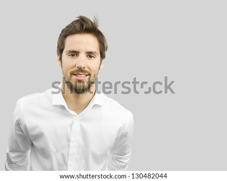 young handsome man smiling isolated over gray background - stock photo