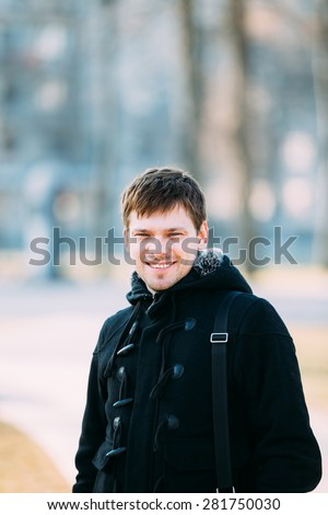 Young handsome man smiling outdoors close up street portrait.