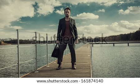 Young handsome man standing on a wharf - stock photo
