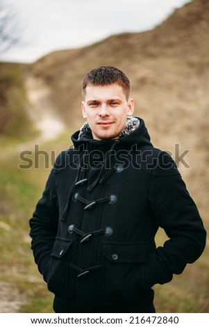 Young Handsome Man Stayed In Field, Meadow In Autumn Day. Casual Style - Jeans, Jacket - stock photo