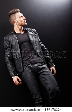 young handsome man. Studio fashion portrait. Posing over black background.No brand.  - stock photo